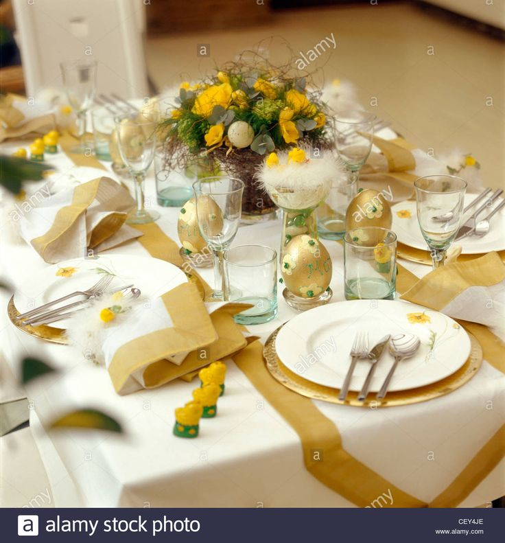 Stock Photo - Tablesetting Easter Dining Table laid, cream tablecloth, gold ribbon runners, pile of white plates, yellow flower pattern.