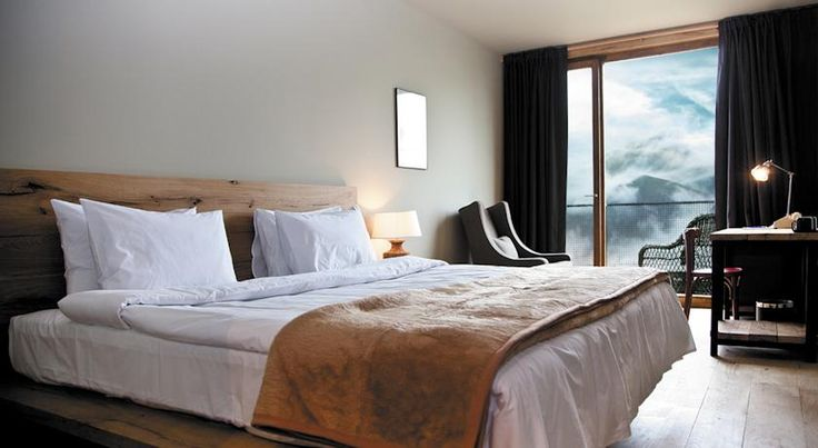 Bedrooms at the Hotel Kazbegi come with incredible views of the local mountains. If look outside isn't your thing, simply enjoy the rustic headboard and leather-lined blanket.
