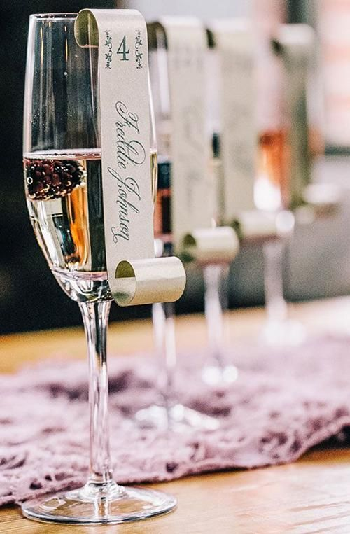 A scroll-style escort card looks chic and elegant perched on the rim of a champagne flute | Brides.com