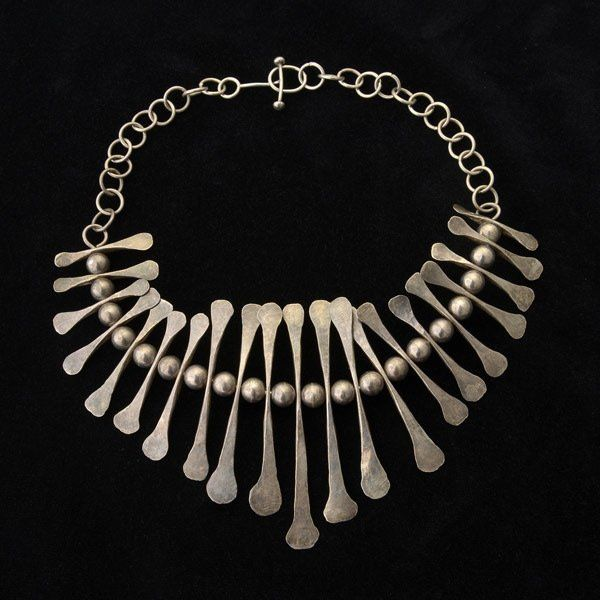 """MID-CENTURY MODERN STERLING SILVER NECKLACE. Featuring twenty-one hammered sterling silver and graduated bone like pendants interspersed with sterling silver balls measuring approximately 9.5 mm, completed by a hand made open link chain with toggle and ring clasp, forming a 19 1/2 inch necklace. Note: Attributed to Fred Farr; a similar necklace is featured on page 90 of """"Modernist Jewelry 1930 - 1960: The Wearable Art Movement"""" by Marbeth Schon."""