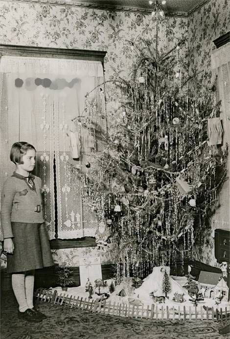 "An unknown little girl by her tree in the early '30s.  Remember those construction-paper chains and ""Japanese lanterns"" we used to make in school and at home while we had the measles?"