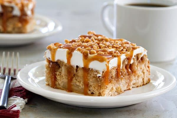 Caramel Apple Poke Cake is topped with whipped topping, caramel sauce, and toffee bits. It doesn't get much better than this!