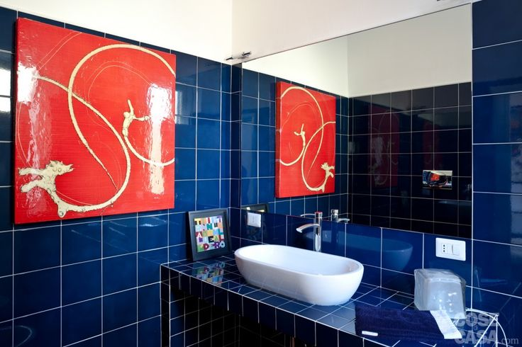 In bagno la monocromia di piastrelle in monocottura lucida blu (Ceramica Bardelli) dà risalto gli altri elementi presenti nella stanza. Su una struttura in muratura poggia il lavabo a catino di forma ovale, modello Aliseo di Ceramica Catalano, completato dal rubinetto El-X di Newform. Il quadro rosso sulla parete è opera di Jonathan Feldschuh, il piccolo arazzo appoggiato sul top è di Alighiero Boetti.