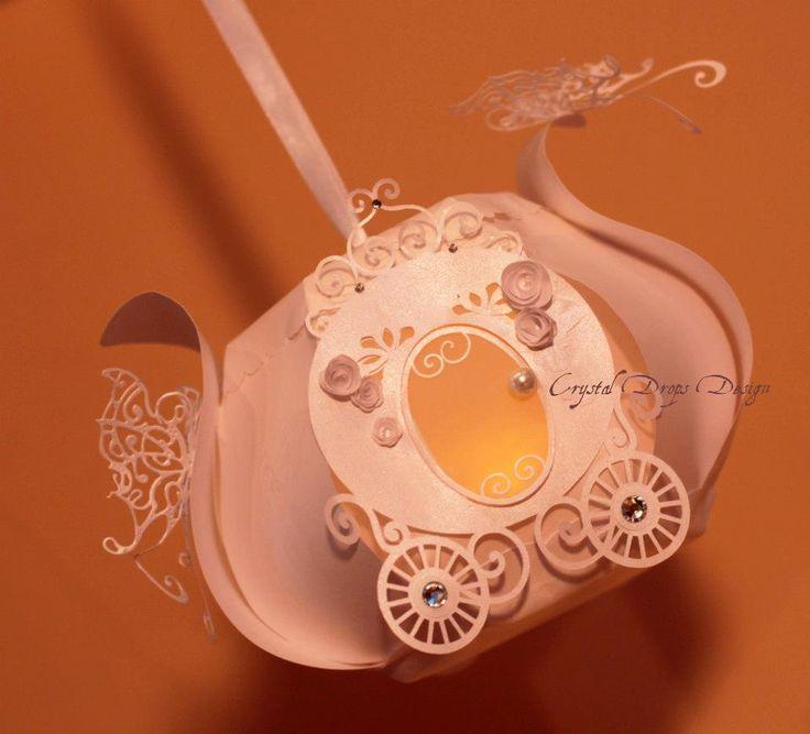 Carrozza lanterna per atmosfere principesche! In preziosa carta perlata ed opalescente con intagli, farfalle filigrana, roselline 3D, perla Swarovski, cristalli Swarovski di 2 dimensioni diverse e nastro in raso per sospenderla.