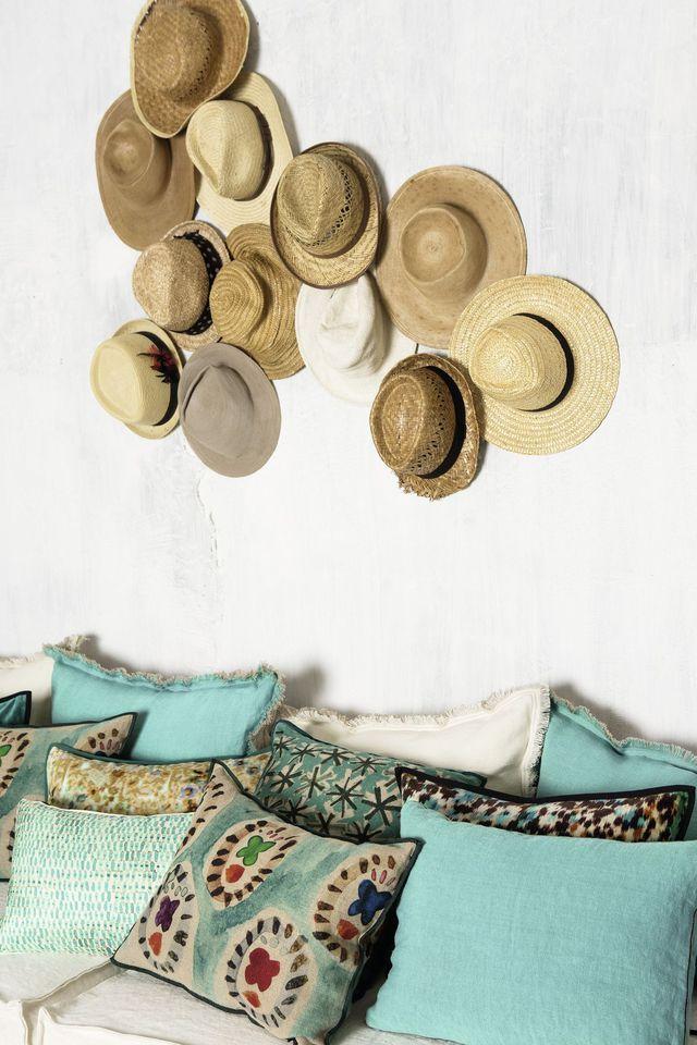 Votre canapé est trop vieux? Choisissez des coussins aux couleurs fraîches et exposez votre collection de chapeaux de paille.