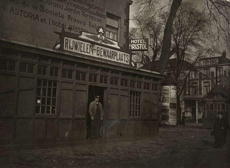Fietsenstalling of rijwielen-bewaarplaats bij station Holland Spoor te Den Haag, Nederland 1913. Foto: Een werknemer staat in de deuropening van de stalling dat onder of naast Hotel Bristol is gevestigd. Rechts op de hoek een 'peperbus en Hotel Terminus aan de overkant.