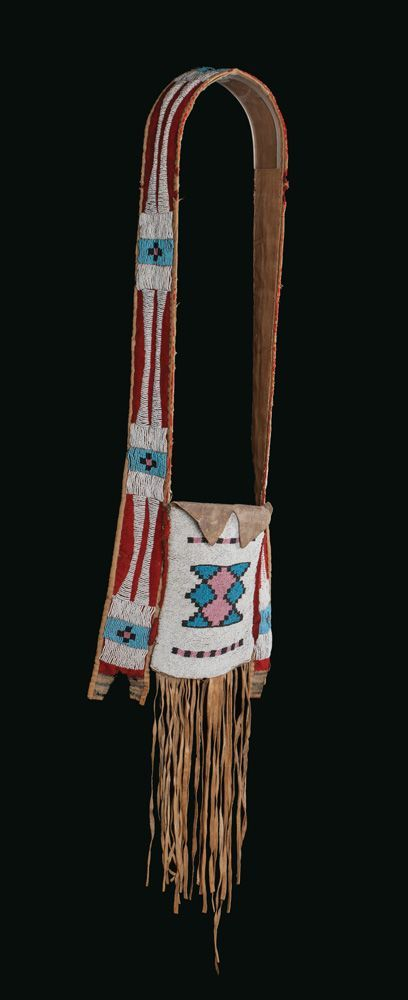 """Assiniboine War Bag. ДА1. Native hide with blue, black, and salmon beads on a white field. Strap has cross and line design with red trade cloth over a canvas backing. 45 1/2"""" x 11 3/4"""" , 14"""" fringe on bottom. Circa 1870. Brian Lebel's High Noon Auction, Jan. 2015."""