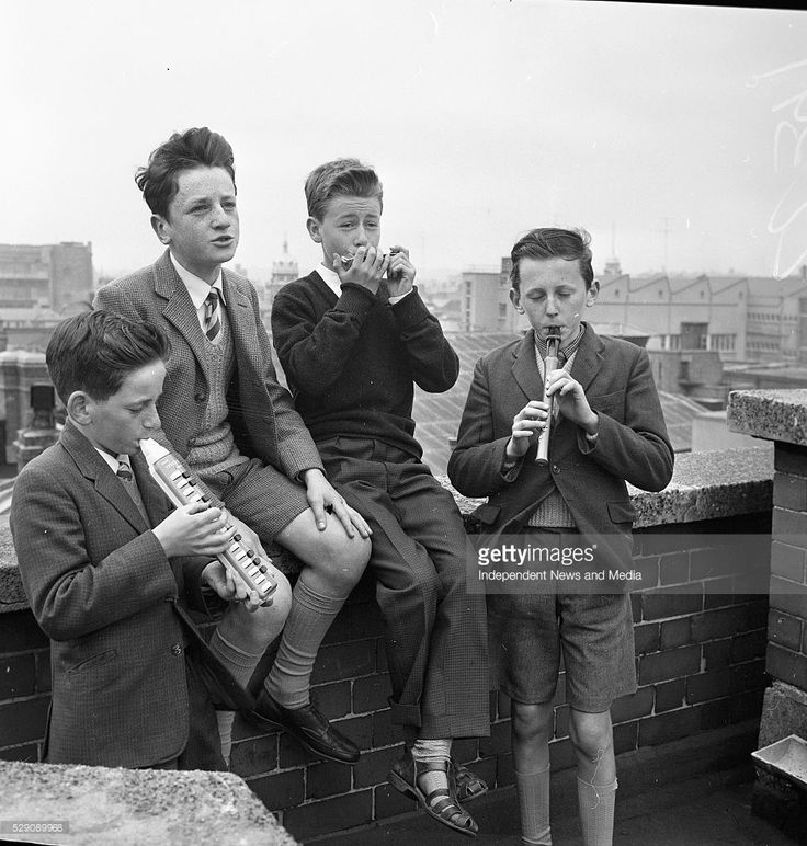 One boy sits on ledge, whilst three other boys play musical instruments, On the roof of Independent Building in Dublin, circa June 1964 (Part of the Independent Newspapers Ireland/NLI Collection).