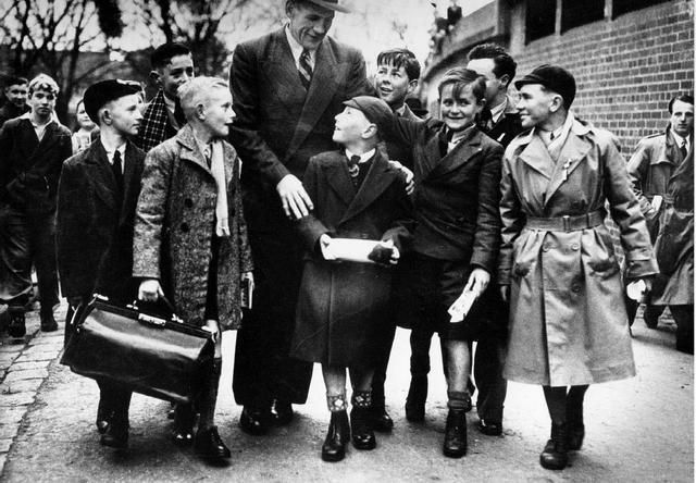 Description: Image held at Richmond Library. The photograph shows Jack Dyer surrounded by a group of admiring boys. Possibly Dyer has just arrived at a football ground since one of the boys is carrying a large bag and people are sitting on top of what may be an outer wall of a stand. Dubbed 'Captain Blood' for his tough play, Jack Dyer was nevertheless one of Richmond's greatest footballers. He played 310 games for The Richmond Football Club between 1931 and 1949.