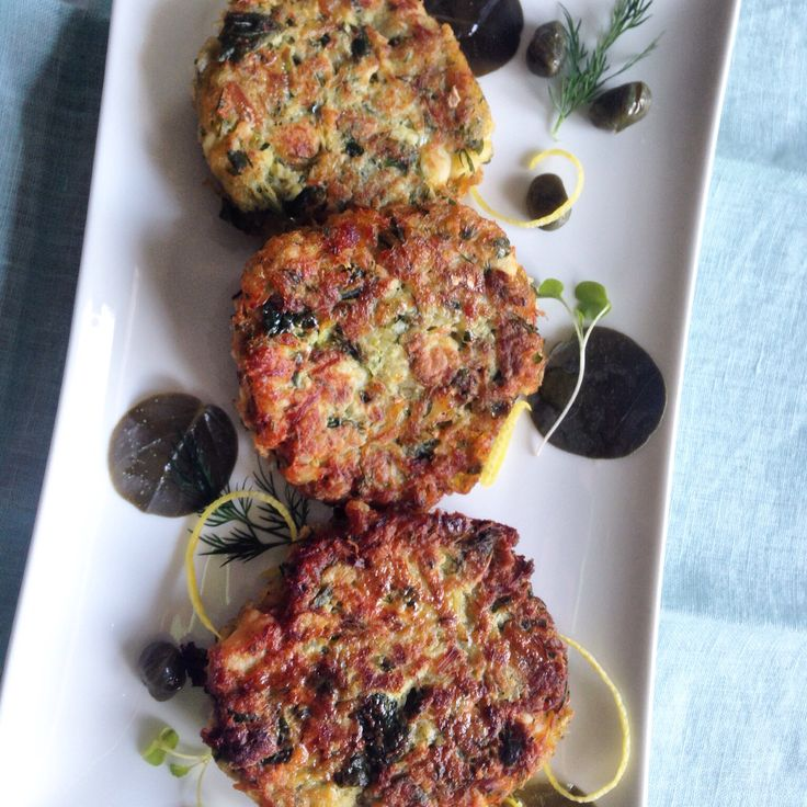 Trio of cod fish cakes with perfectly brined capers and caper leaves from the Island of Santorini .