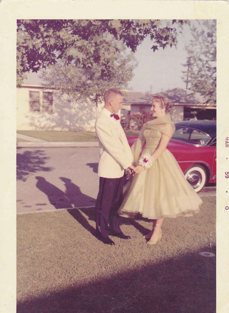 Vintage prom photo 1959 found photo street style late 50s evening dress cocktail length gold yellow green tulle satin couple stand next to car vintage fashion style mens suit white coat