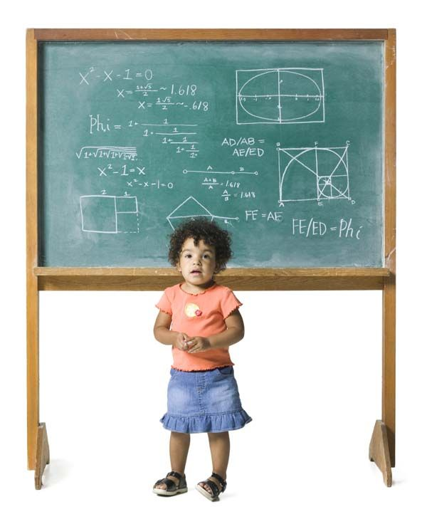 A photo of a two-year-old girl standing in front of a chalkboard that has a complex math problem written on it. The little girl holds a piece of chalk.