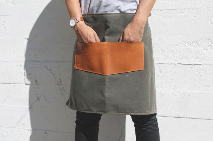 "This handmade waxed canvas and leather apron is as utilitarian as it is eye catching. Hold your cookware, tools, or gardening gloves in the oversized leather pockets that will just improve with age. A great gift for the craftsman.  Dark Olive Waxed Canvas 5-6oz Latigo Leather 29""W x 18.5""H Adjustable Leather Waist Strap Hand Made Copper Rivets  2 Pockets Measuring 7"" x 5.5""  Handmade in Santa Cruz"