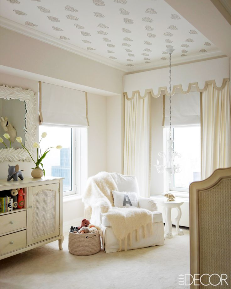 All-white nursery with wallpaper on the ceiling and traditional, antique furniture