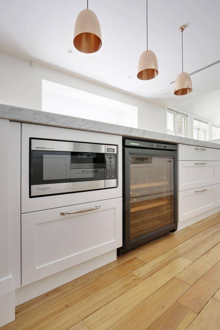 A microwave built in using a custom frame alongside a freestanding Liebherr Wine fridge