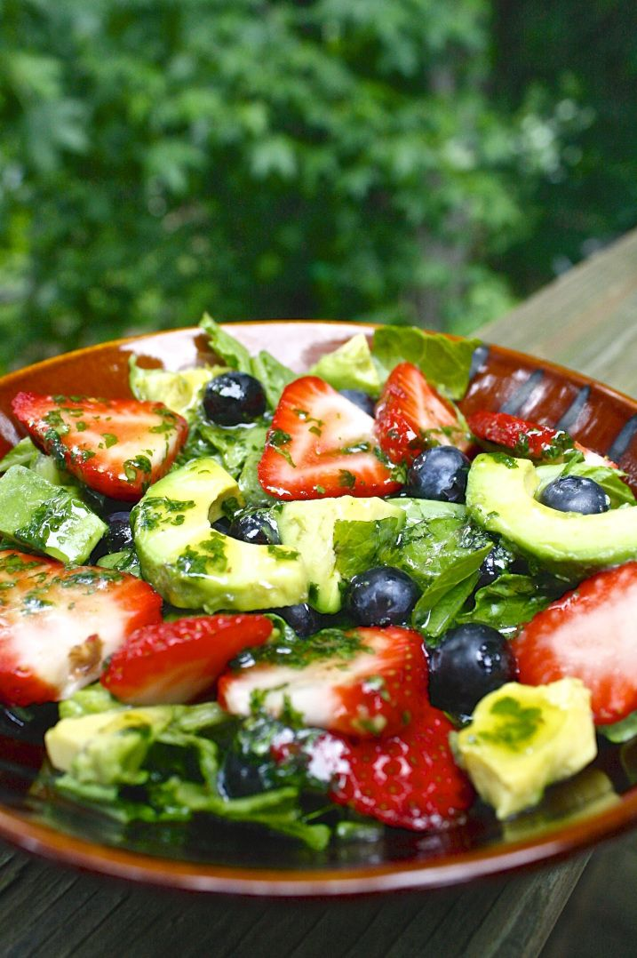 Summer salad with avocado, strawberries, blueberries and cilantro dressing.