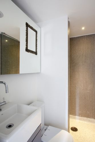 O piso da pequena área molhada foi executado em granilite claro, e as paredes, no box para chuveiro, receberam pastilhas de porcelana Jatobá