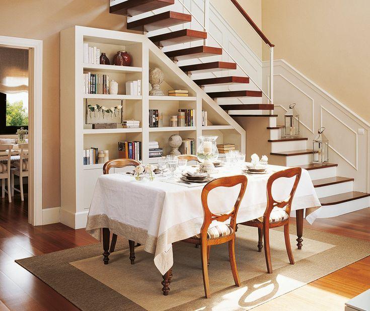 El hueco de la escalera se ha aprovechado para montar un mueble a medida y crear una zona de comedor. Una alfombra ayuda a delimitar el espacio.