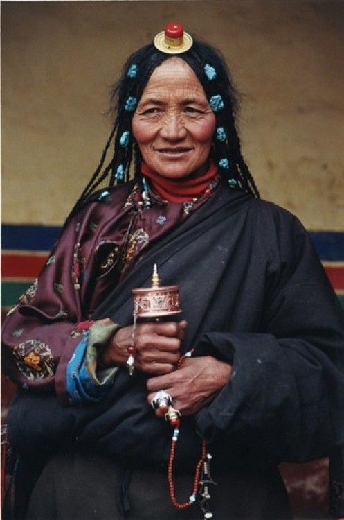 Tibetan elderly woman holding a prayer wheel.