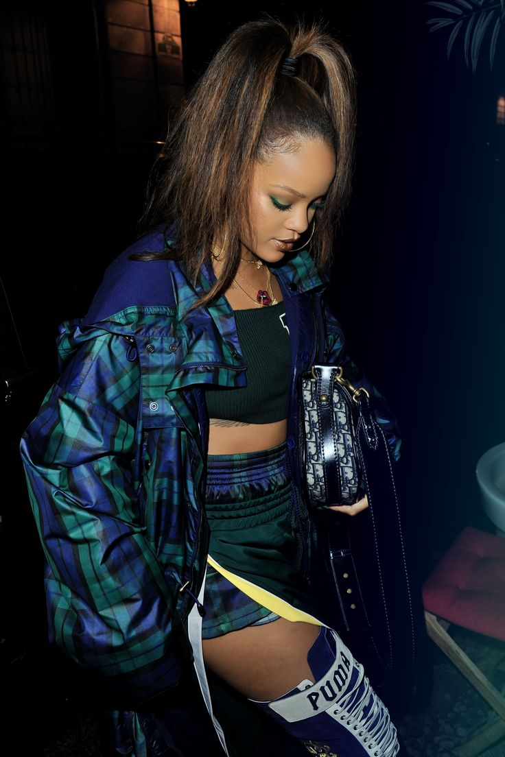 Rihanna wearing green plaid, outfit, blue and white puma boots.