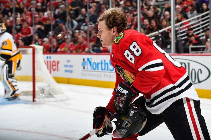 Patrick Kane #88 of the Chicago Blackhawks skates up the ice carrying his helmet