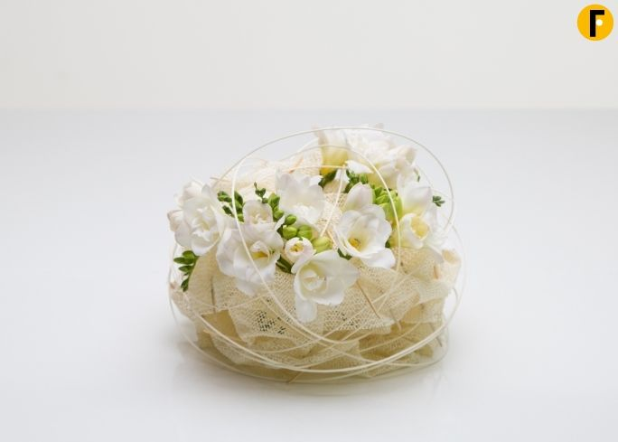 Soft knot - Floral design with white Freesia While shopping, Nelleke came across an anti slip mat, that inmidiately gave her an idea to use for the Freestyle day with Freesia. A glass container is covered with the anti slip mat and pierced with small sticks for many times. Doing this the material starts to look like a soft knot and keeps it that way. Afterwards the freesias are placed in between. Easy, do-able and controversial for your customers.