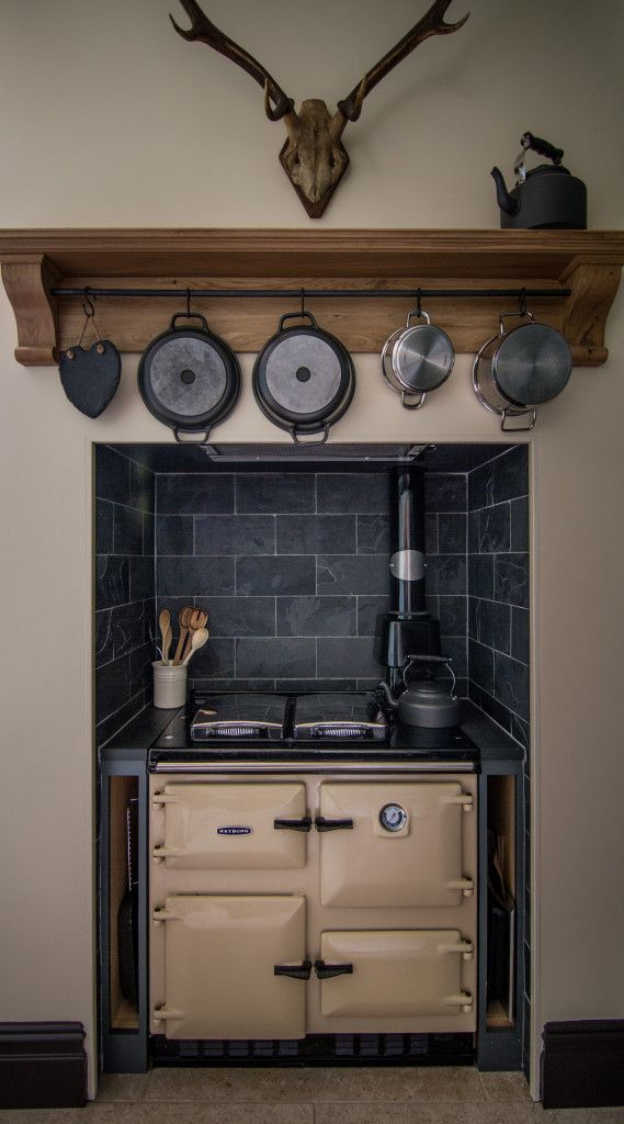 Sustainable Kitchens - Cotswold Chapel Kitchen. A cream Rayburn sits in this alcove with a slate tiled splashback. An oak mantelpiece sits stylishly above, with hanging rail for pots and pans. Steve the antlers adds a rustic country accent.