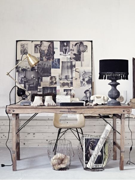 Rustic neutral workspace with metallic and black accents. Timber desk, wire baskets, collage moodboard and tasselled lamp shade.