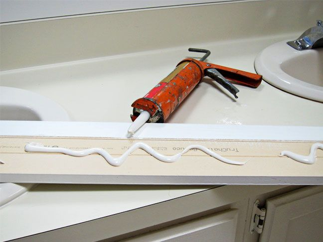 adding trim to a mirror using liquid nails.  Tutorial included for using no-miter moulding.