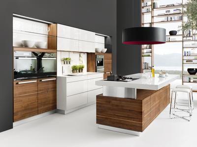Bijzondere keuken in wit en hout. Deze keuken is een bijzondere verschijning. Doordat de kasten van het witte middengedeelte uitsteken, heb je daar meer bergruimte en een lekker ruim werkblad. Het overhangende werkblad van het kookeiland zorgt ervoor dat je meteen een handige plek hebt om aan te ontbijten. De grote zwarte ronde afzuigkap is meteen verlichting.