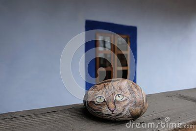 Ornamental handicraft painted stone cat over a wooden balustrade of an old romanian house