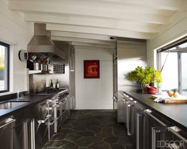 In the screening house, the kitchen's range and vent hood are by Viking, as are the handles on the stainless-steel cabinetry.