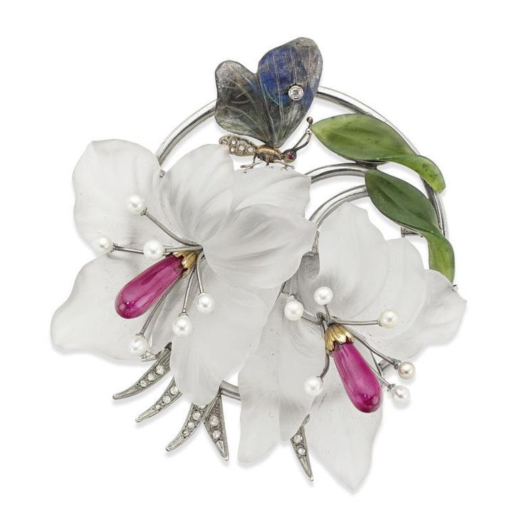 A mid 20th century gem-set brooch, by Kern, Vienna Formed as a spray of exotic lilies with carved rock crystal petals and cultured pearls and synthetic ruby stamens, the circular foliate border set with rose-cut diamonds and carved nephrite leaves, with a small diamond and carved labradorite butterfly resting on the petals, width 69mm, stamped '585', 'H.K' and signed 'KERN, WIEN', to original fitted case, Bonham's