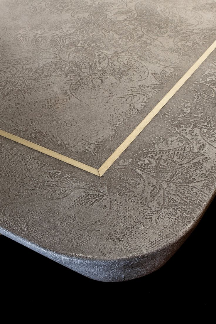 Dialogo Table detail - Del Bello Collection. Surface XENSUM thickness 42 mm inclined border and rounded, chamfered corners. Insert in brass brushed by hand. Structure in hand coated metal, composed of inclined legs and semi circular base.