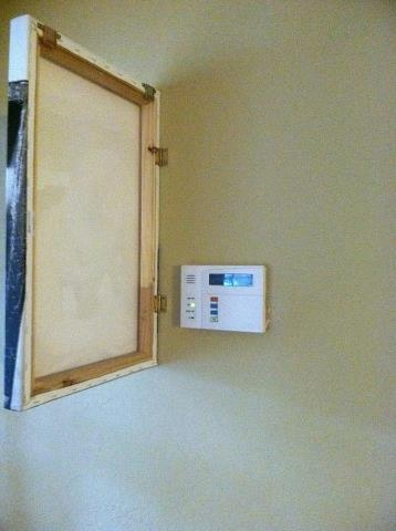 Put hinges on a canvas and attach it to the wall to cover unsightly controls like security alarms or even unused light switches. NOTE: Not ideal for thermostats.