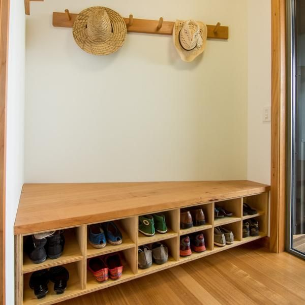 Solid macrocarpa and plywood shoe/coat/jacket storage is a warm and functional welcome to this home