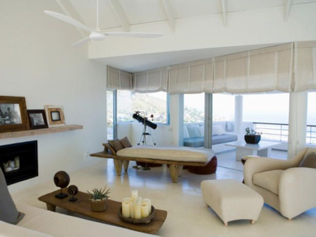White linen Roman shades cover the windows and contribute to the soft, all-white decor of this modern living room.