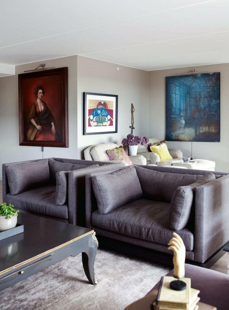 KUNST PÅ ALLE VEGGER: I tillegg til det mestnødvendige som lenestoler, sofa, bord og teppe, er stuen rikt møblert med kunst. Det store blå er signert Elisabeth Werp, i midten en Pushwagner, og det rødemaleriet er et selvportrett av kunstnerenTrine Folmoe. Hvite stoler fra Englesson og Verket Interiør, de lilla stolene er fra Christian
