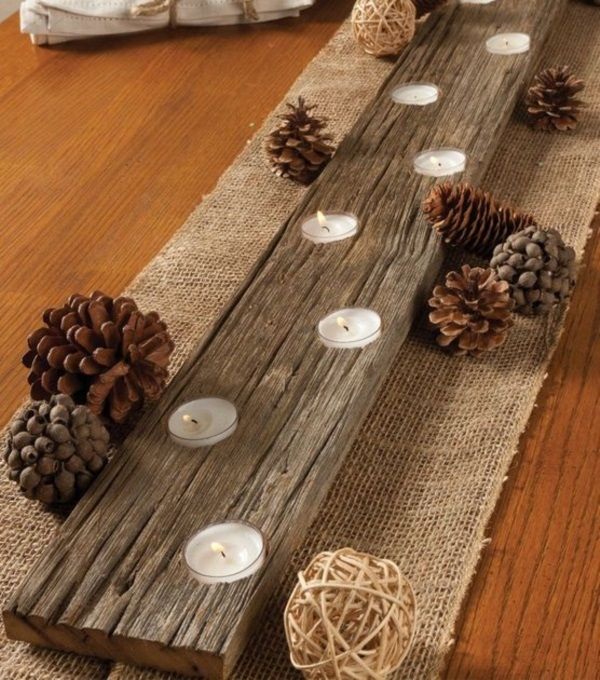 I love this wood beam dining table runner with pine cones and candles! It's perfect for a rustic or country theme.