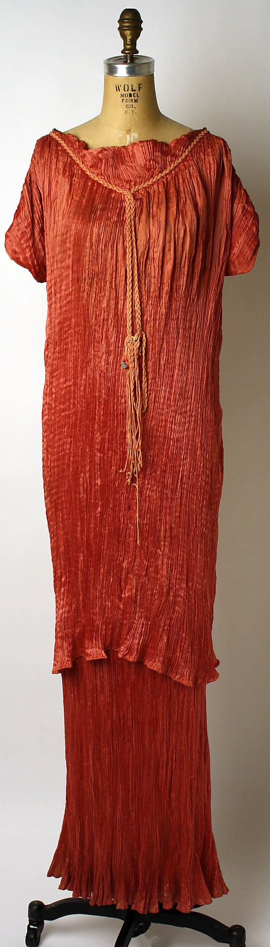 Los Delphos fueron confeccionados en el formato plisado: unos finísimos pliegues - posiblemente inspirados en las korai griegas- realizados directamente sobre el propio tejido en todo su largo, abarcando al vestido completo. Al caer libremente sobre el cuerpo, los pliegues se iban abriendo o cerrando en función de las formas de la modelo y remarcaban totalmente la figura. Delphos de  Mariano Fortuny, 1936.