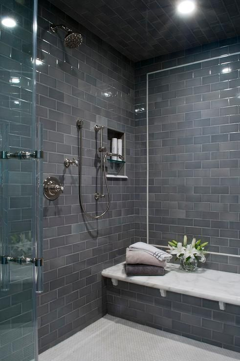 Contemporary shower boasts a gray subway tiled ceiling and walls lined with a white marble top bench alongside a white marble hex tiled shower floor.