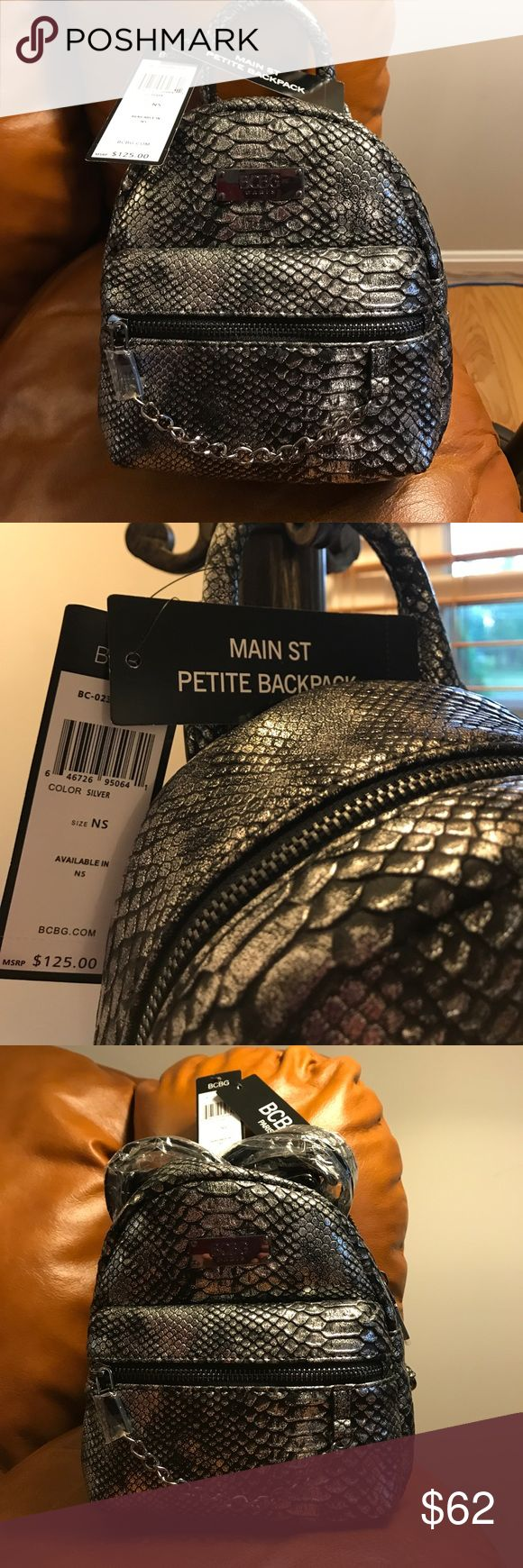 "BCBG MINI BACKPACK SILVER NWT BCBG MINI BACKPACK SILVER NWT. Main Street Petite Backpack. Silver. Snakeskin Silver Patten. Brand new with tags and wrapped straps. Front pocket. 1 slip pocket inside. Adjustable straps. Top Handle. Approx 7"" w x 8"" x 3"" deep. BCBG Bags Mini Bags"