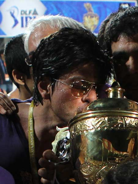 Bollywood star and co-owner of Kolkata Knight Riders Shah Rukh Khan kisses the DLF IPL 2012 cup as he celbrates his team's victory at the end of the IPL Twenty20 cricket final match, between Chennai Super Kings and  Kolkata Knight Riders at The M.A.Chidambaram Stadium in Chennai on May 27, 2012.