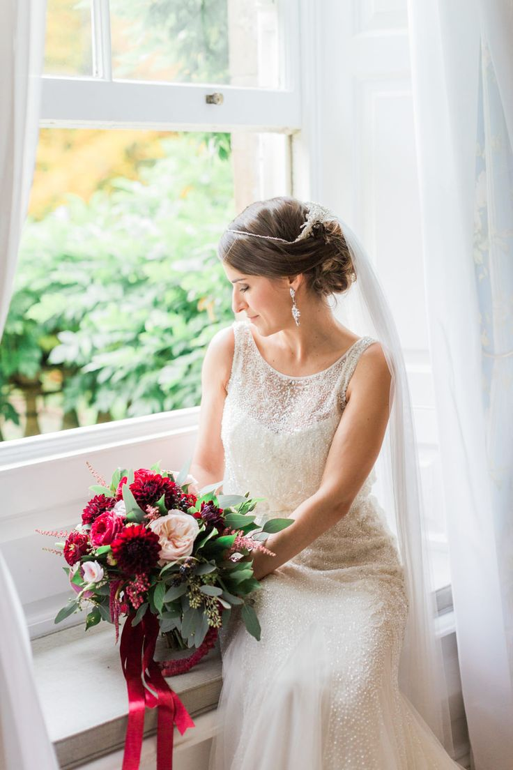 Bride In Rosa Clara Wedding Dress With Red Bouquet