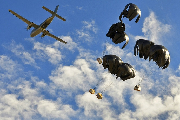 """""""Dinner's Here!"""" Food, fuel and other vital supplies are air-dropped to Forward Operating Base Lightning deep in the mountains of Paktya province Dec. 23. The military said poor weather – not the insurgency – was the reason for the special delivery."""