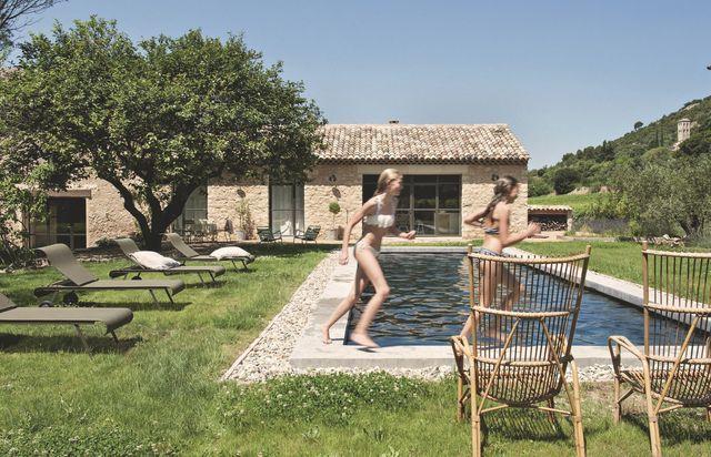 La bâtisse mêle pierres sèches et baies en serrurerie métallique, Hugon à Nîmes. Dans l'axe du salon, la piscine en béton gris dessinée par Marie-Laure. Chaises longues Fermob et fauteuils vintage en osier.