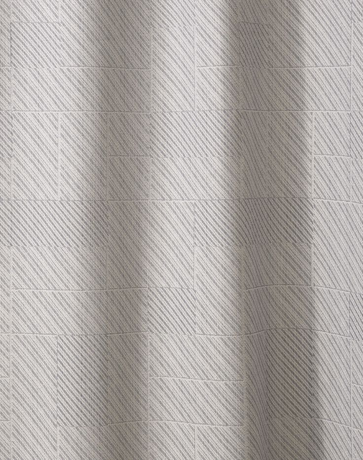 Jacquard-woven diagonal lines. The pattern of the curtain Utopia is inspired by the surface of concrete, glass and weathered metal.