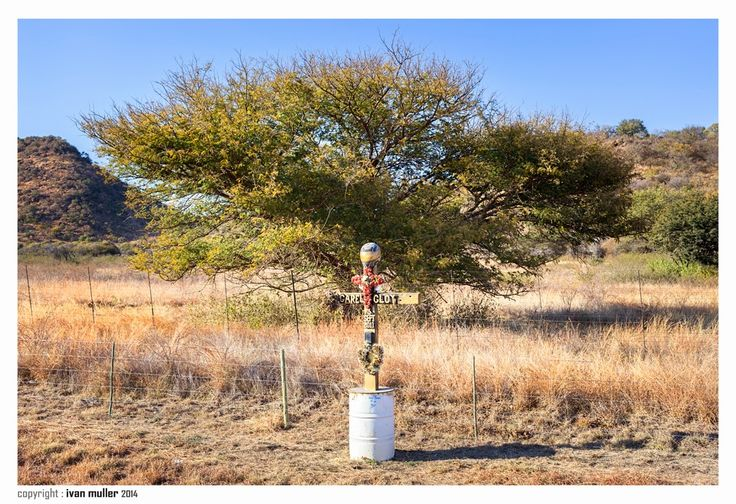 On the road to Rustenburg a lone marker Carel Gloy -   3 Sept 2011. A new phenomenon here in South Africa to mark the scene of a fatal accident with some sort of shrine, usually a wooden crucifix, like the one here marked with the name of the deceased and even a motorcycle helmet.