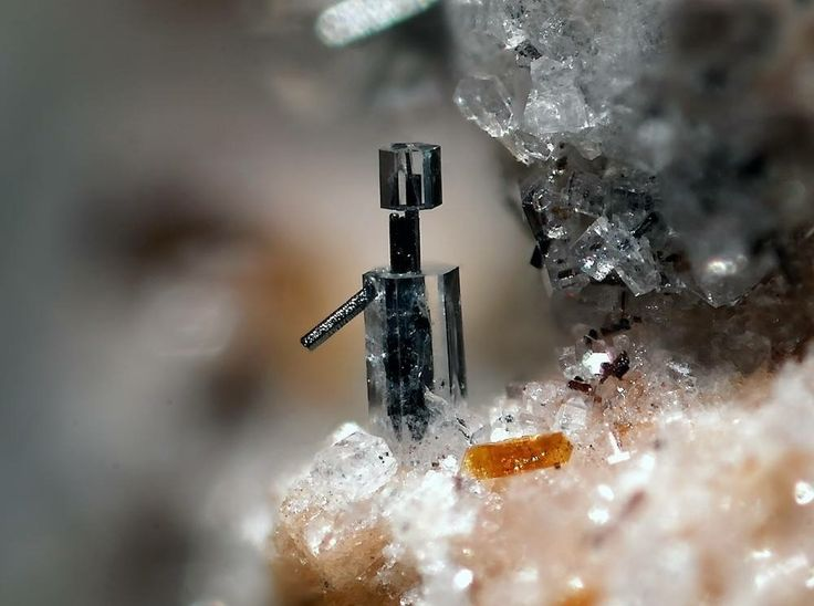 Nepheline grown around a Hematite crystal (Image width: 2 mm), Eifel region, Germany photo: Fred Kruijen  Geology Wonders