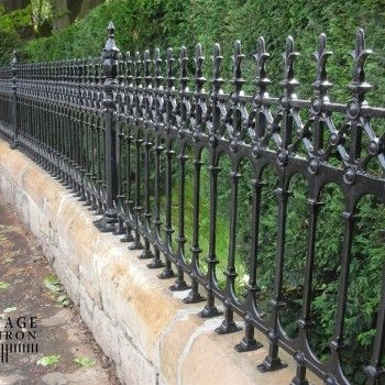 Stone wall & cast iron fencing. Fence by Heritage Cast Iron USA.
